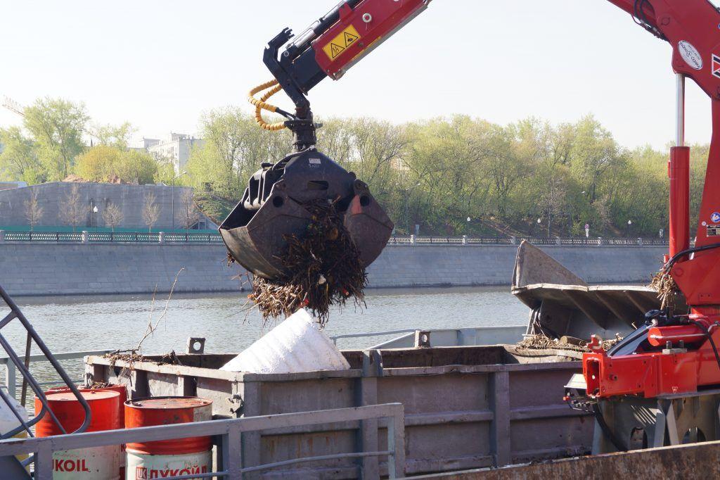 кран собирают мусор на реке