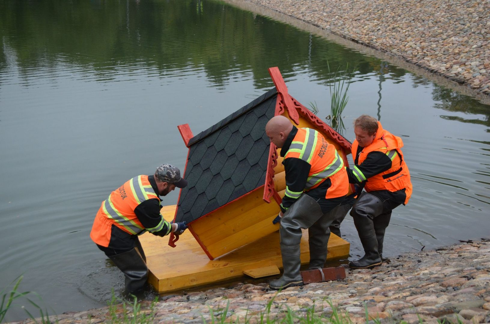 """Сотрудники ГУП """"Мосводосток"""" устанавливают на плавучую платформу утиный домик. Все берега столичных прудов теперь имеют удобный выход для утят на берег."""