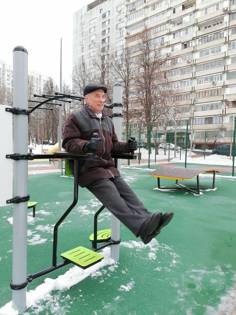 Пенсионер Евгений Николаевич занимается на спортивном снаряде, сквер, зима, дети, сквер Победы, благоустройство