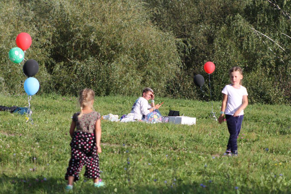 Маленькие гости детского праздника на открытом воздухе под присмотром мамы