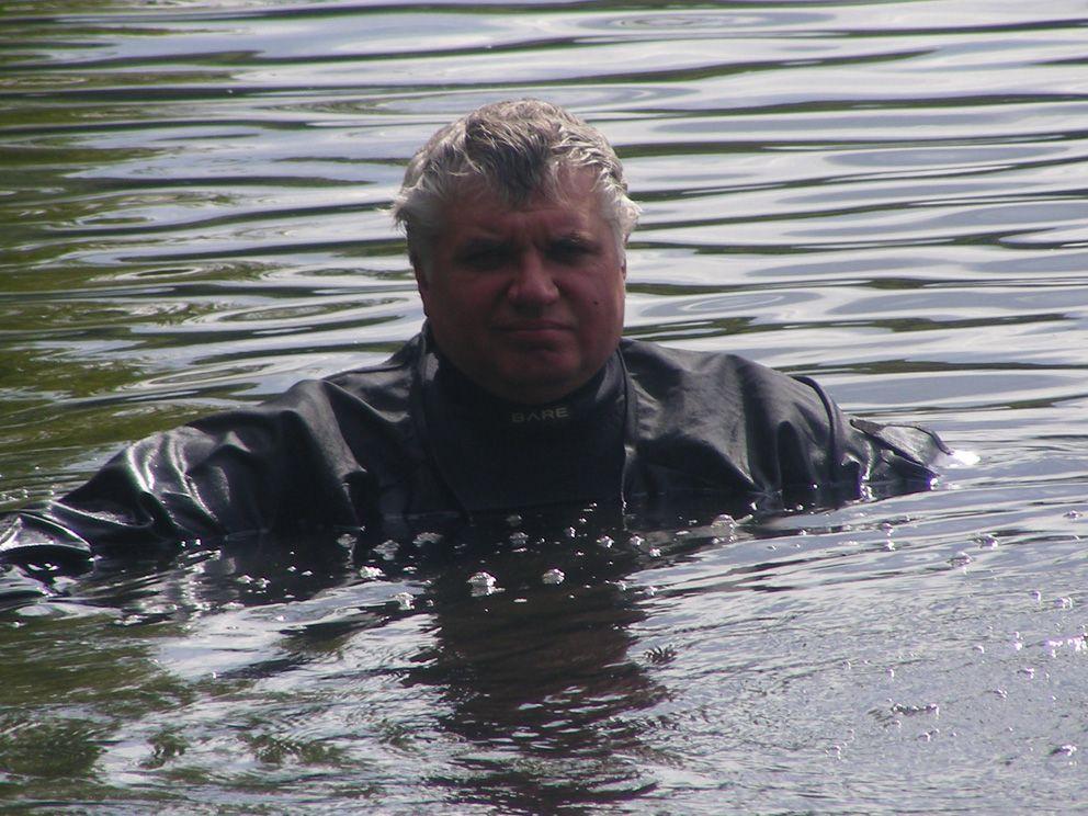 Водолаз Михаил Грекулов с поверхности подает коллеги, который под водой проводит резку металла. Обратите внимание, как бурлит вода и на поверхность со дна поднимается «дым»
