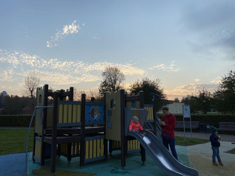 Радостный ребёнок скатывается с горки на благоустроенной детской площадке в «Коломенском»