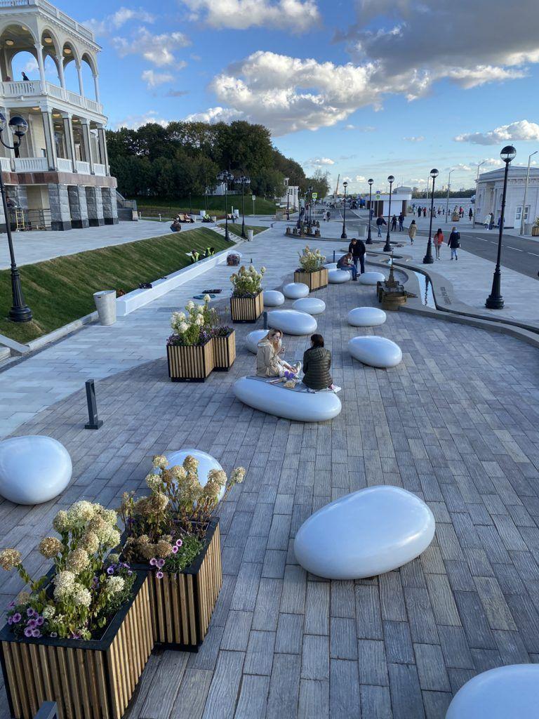 Посетители прогуливаются возле декоративных камней и цветочных клумб на набережной