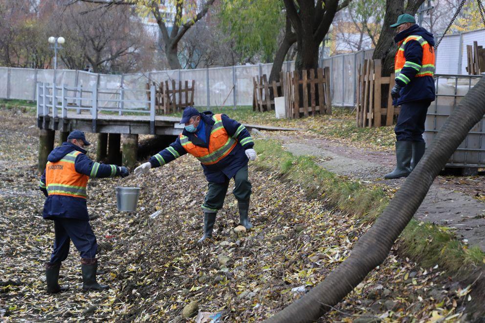 Рабочие передают ведро с рыбами коллеге на берег