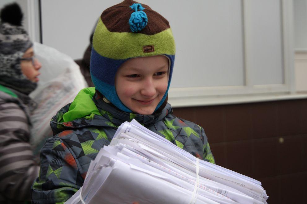 Мальчик собрал целую кипу белой бумаги