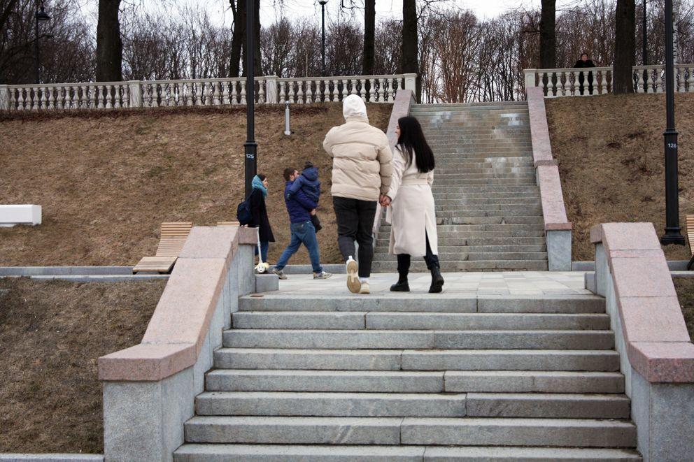 Влюбленные пары и семьи с детьми с удовольствием проводят время в парке